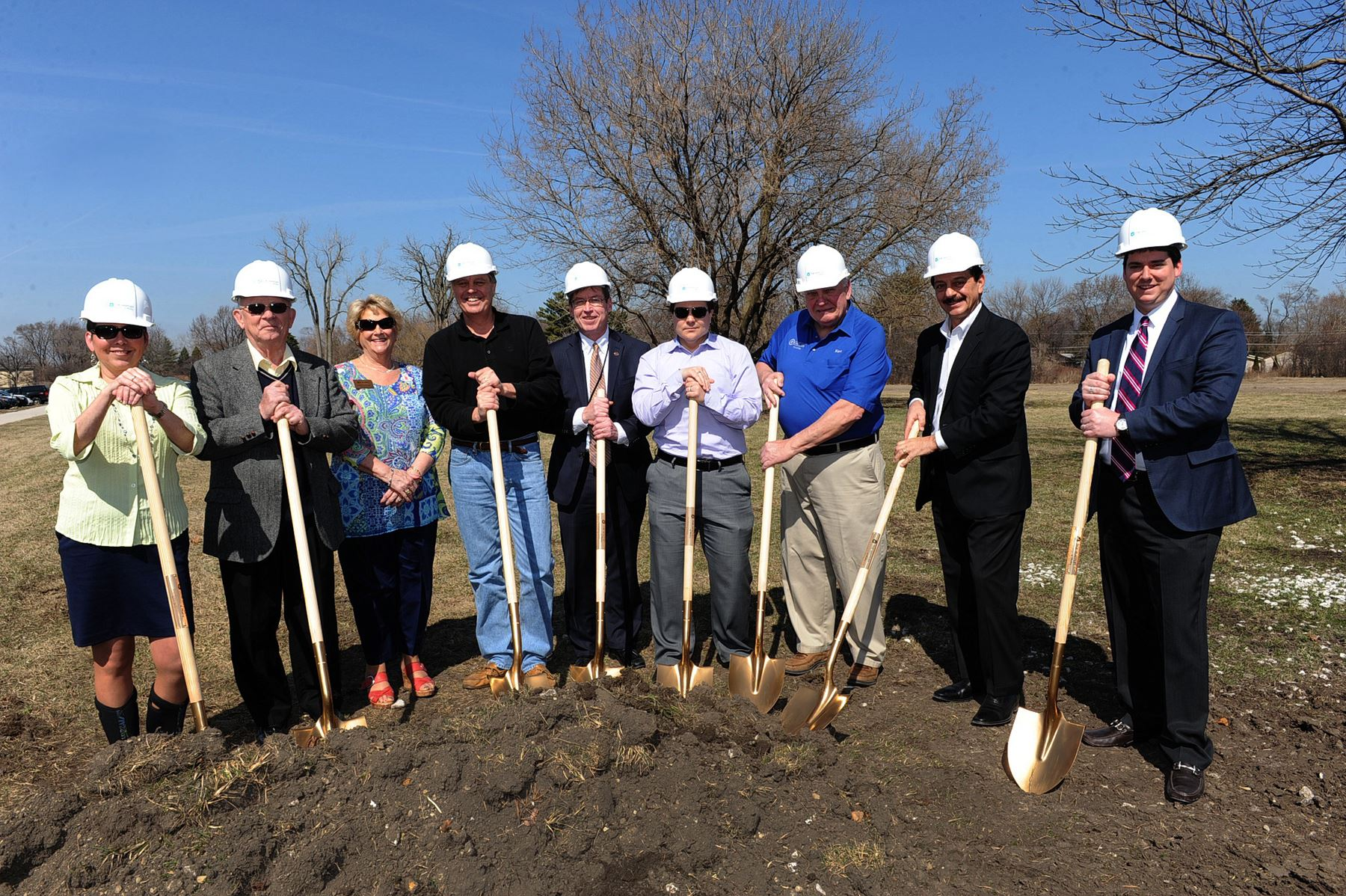 Representatives hold shovels and wear hard hats at the Whitley Groundbreaking Ceremony