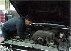 Person under the hood of a car fixing the engine