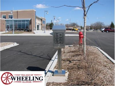 "A drop-box in front of a building, with the watermark, ""Village of Wheeling, Illinois."""