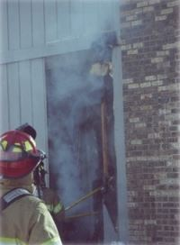 Firefighters fight smoke coming through a doorway
