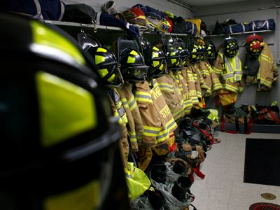 Firefighter uniforms and fire attire hung up on hooks